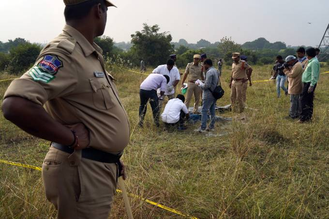Forensic officials examine the bodies at the site where police shot dead four men suspected of raping and killing a 27-year-old veterinarian, in Chatanpally on the outskirts of Shadnagar