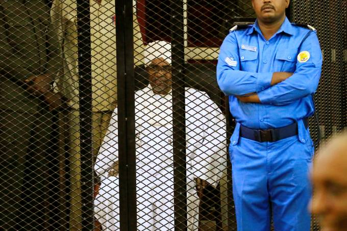 Sudanese former president Omar Hassan al-Bashir sits inside a cage during the hearing of the verdict that convicted him of corruption charges in a court in Khartoum