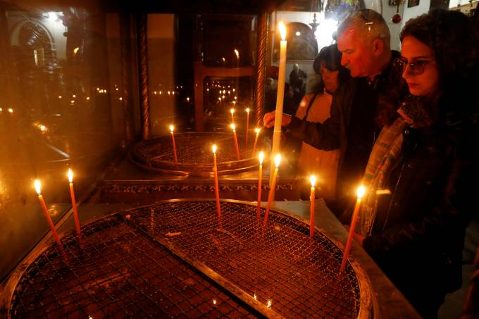 Visitors light candles in the Church of the Nativity in Bethlehem in the Israeli-occupied West Bank