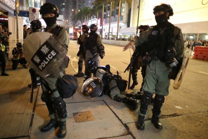 Police detain a Hong Kong protester at a march in Hong Kong