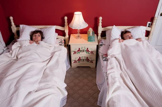 Young couple hiding under bedclothes – casal – camas separadas