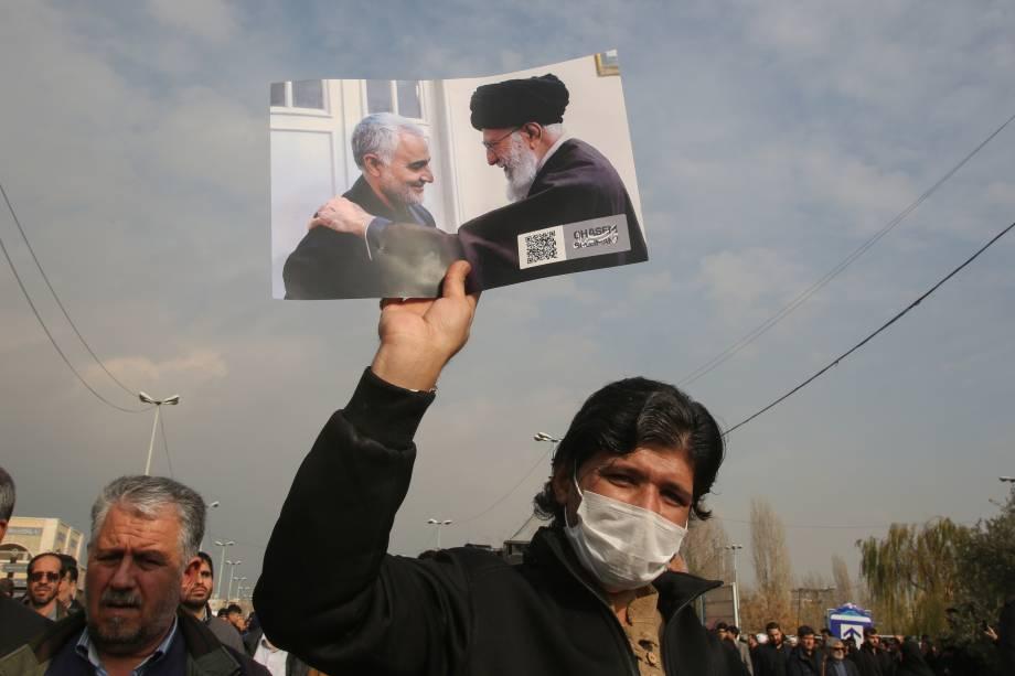 Um iraniano ergue uma foto do Supremo líder, aiatolá Ali Khamenei, ao lado do general Qassem Soleimani, morto em um ataque aéreo dos Estados Unidos - 03/01/2020
