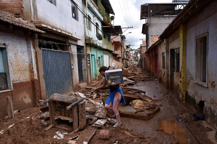 Um morador local caminha entre escombros após o transbordamento do córrego Da Prata devido a chuvas torrenciais, em Raposos, região metropolitana de Belo Horizonte, em 28 de janeiro