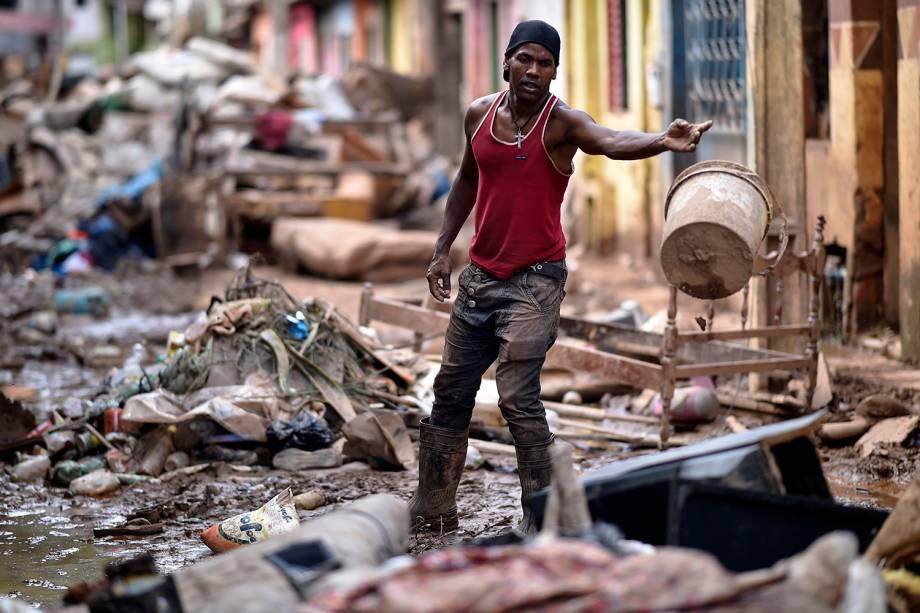 Wanderley Vieira tenta limpar os escombros após o transbordamento do córrego Da Prata, em 28 de janeiro