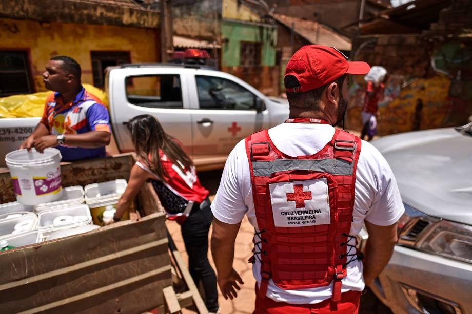 Membros da Cruz Vermelha do Brasil distribuem água e material de limpeza para os moradores locais, após o transbordamento do córrego Da Prata devido a chuvas torrenciais, em Raposos, região metropolitana de Belo Horizonte, em 28 de janeiro