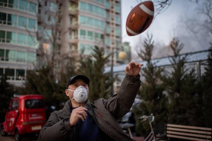 Homem joga futebol americano de máscara em Pequim