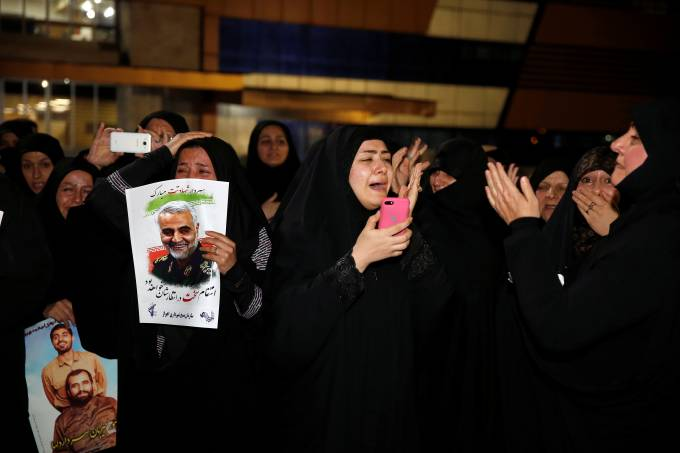 Iranian mourners react upon the arrival of bodies of Soleimani