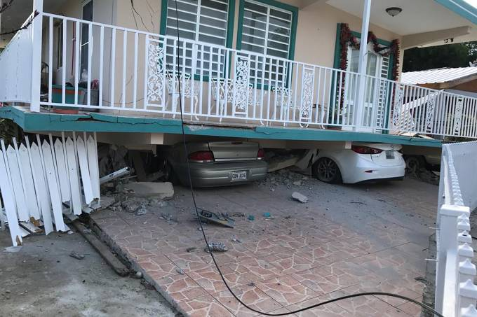 Cars lie under a collapsed house after an earthquake in Guanica