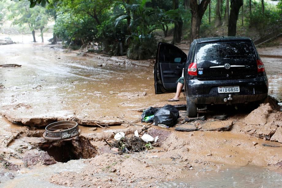 Carro e rua danificados são retratados após fortes inundações causadas por chuvas em Belo Horizonte, 29 de janeiro