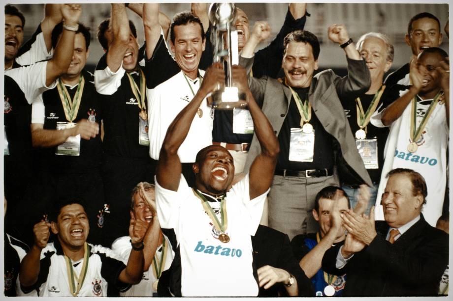 Rincón segurando o troféu do Campeonato Mundial da Fifa, com o presidente Alberto Dualib, à direita, e a equipe do Corinthians ao fundo