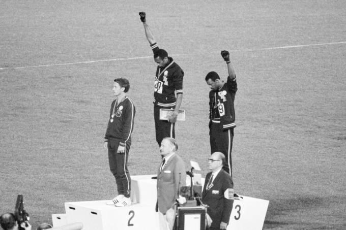 Os atletas americanos Tommie Smith e John Carlos (1º e 3º lugar) fazem sinal em protesto, nas Olimpíadas do México em 1968
