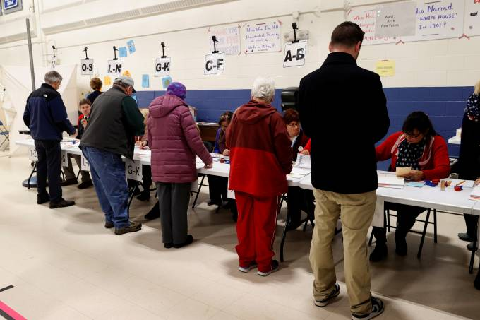 Voters check-in before casting their ballots in the New Hampshire U.S. presidential primary election at the Webster School, in Manchester