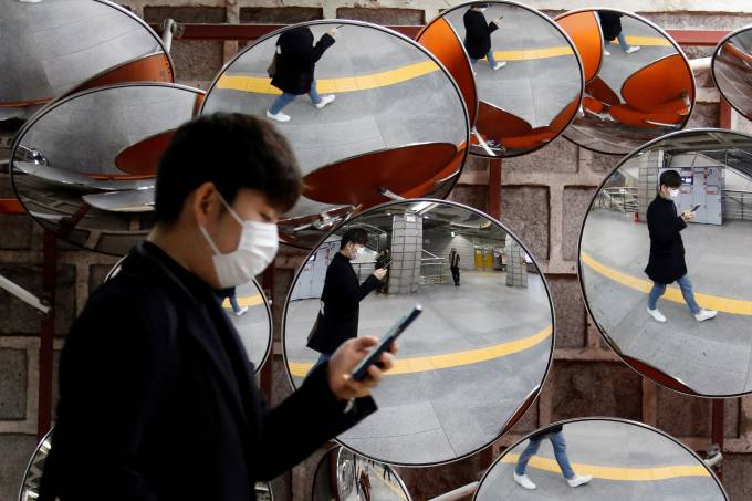 Man wearing a mask to prevent the coronavirus is reflected in the mirrors, in Seoul