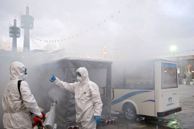 Members of the medical team spray disinfectant to sanitize outdoor place of Imam Reza's holy shrine, following the coronavirus outbreak, in Mashhad