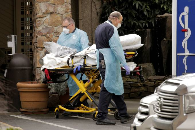 Medics transport a person on a stretcher into an ambulance at the Life Care Center of Kirkland, a long-term care facility linked to several confirmed coronavirus cases, in Kirkland