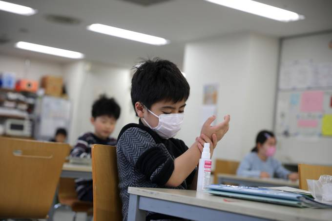 "Child, wearing a protective face mask, following an outbreak of coronavirus, uses hand sanitizer at ""Stella Kids"", daycare center in Tokyo"