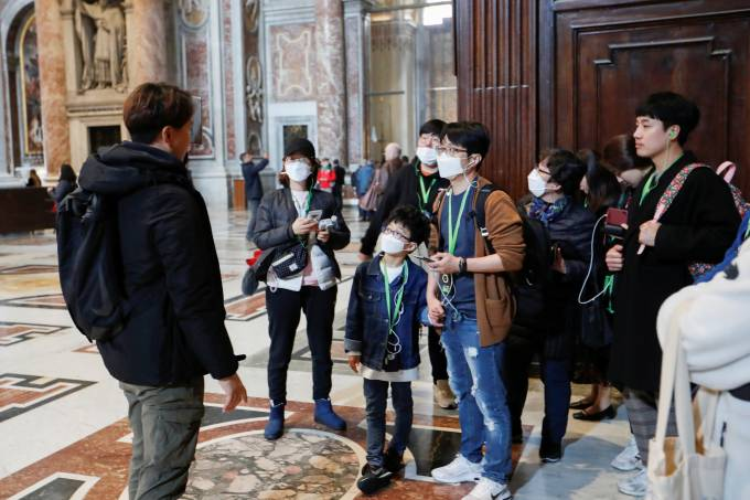 Turistas usam máscara de proteção durante visita à Basílica de São Pedro, no Vaticano