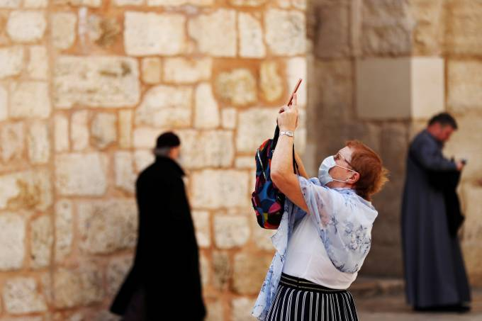 A worshipper wears a face mask for protection releted to the coronavirus as she takes a picture at the entrance to the Church of the Holy Sepulchre in Jerusalem's Old City