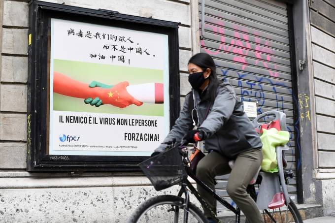 A woman, wearing a protective face mask, rides a bicycle past a placard after a decree orders for the whole of Italy to be on lockdown in an unprecedented clampdown aimed at beating the coronavirus, in Milan