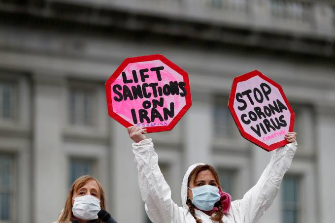FILE PHOTO: People attend a protest against the role that U.S. sanctions plays on Iran and the exacerbation of the coronavirus disease (COVID-19) worldwide, as the World Health Organization said for the first time on Wednesday that it now sees the coronavi