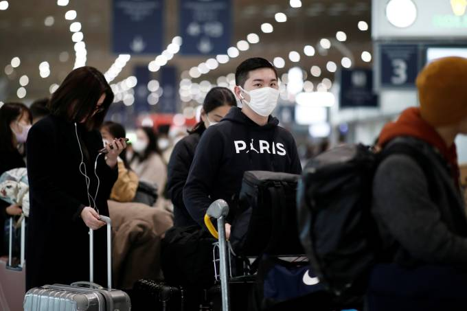 Masked travellers stand in line with luggage before getting to the Air France ticket counter at Paris Charles de Gaulle airport
