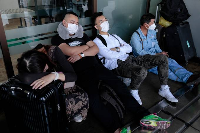 Foreigners wearing masks sleep outside the Ninoy Aquino International Airport in Paranaque, Metro Manila, amid fears of coronavirus disease (COVID-19) spreading in Philippines