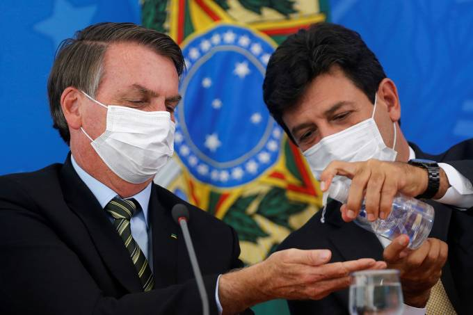 Brazil's President Bolsonaro and Minister of Health Mandettas, wearing protective face masks, sanitize their hands during a news conference to announce measures to curb the spread of the coronavirus disease (COVID-19) in Brasilia