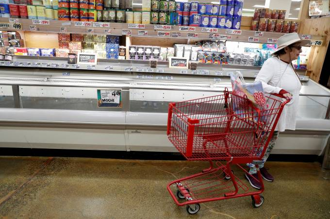 "A woman stands with an empty shopping cart, prior to California's Governor Gavin Newsom's effective immediately statewide ""stay at home order"", in the face of the fast-spreading pandemic coronavirus (COVID-19), at Trader Joe's in Napa, California"