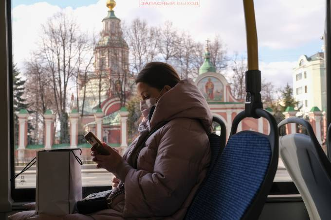 A woman wearing a protective mask sits in a bus in Moscow