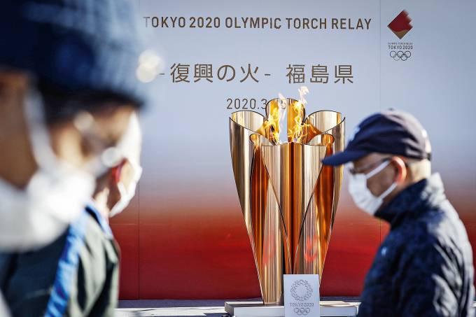 Olympic cauldron is seen behind visitors wearing protective mask in Iwaki, Fukishima