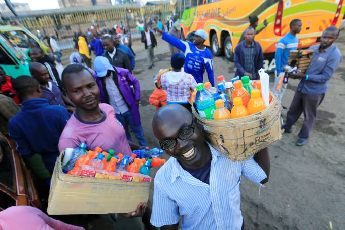Hawkers sell soft drinks to passengers as residents leave for the villages amid concerns over the spread of coronavirus disease (COVID-19) in Nairobi