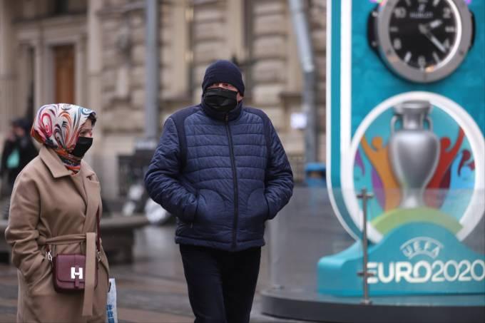 Casal usando máscaras ao lado do logo da Euro-2020 em São Petersburgo, na Rússia