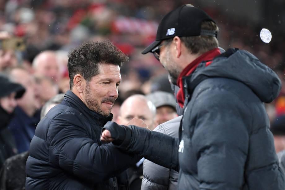 Diego Simeone, do Atlético de Madrid e Jurgen Klopp, do Liverpool, evitam o toque de mão ao se cumprimentarem antes do confronto em Anfield