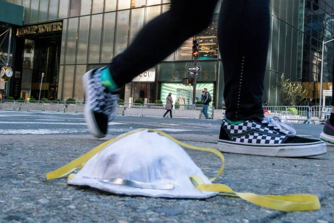 A woman walks by a face mask used to protect from the coronavirus disease (COVID-19) is seen on the ground near Trump Tower in New York City, New York