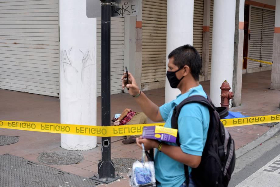 Um homem oferece máscaras à venda perto do corpo de um homem que desabou na calçada, durante o surto de coronavírus