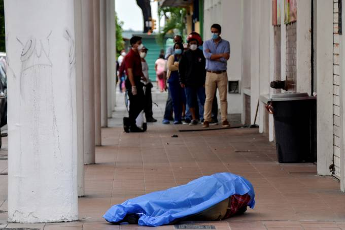 People stand in line outside a shop near the dead body of a man who had collapsed on the sidewalk, during the outbreak of the coronavirus disease (COVID-19), in Guayaquil