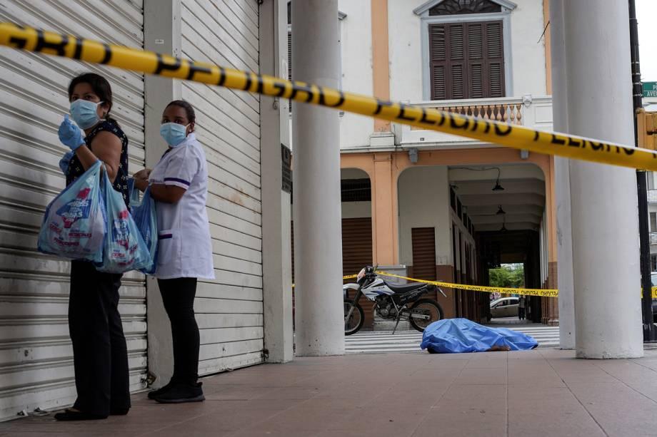 Mulheres próximas ao cadáver de um homem que desmaiou na calçada, durante o surto de coronavírus (COVID-19), em Guayaquil, no Equador