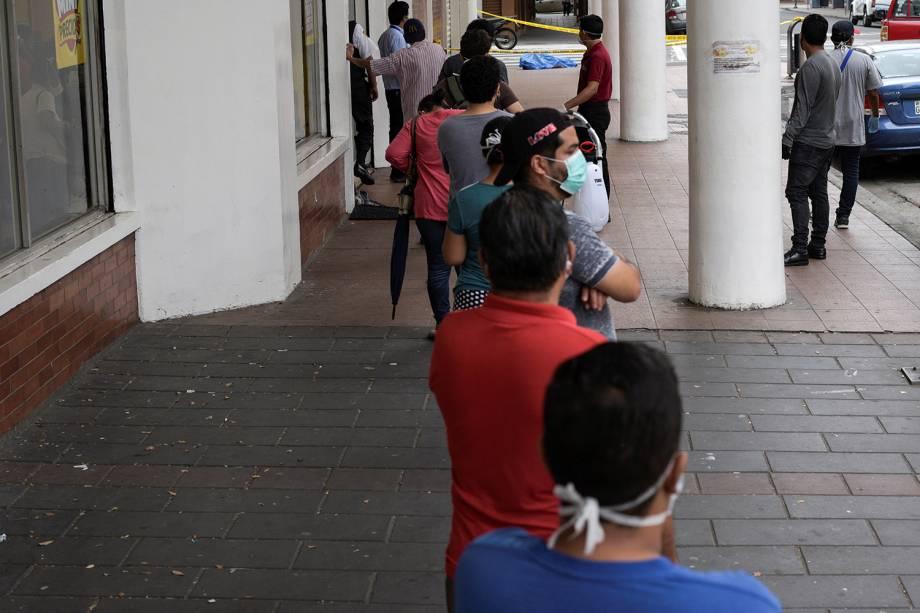 Pessoas ficam na fila em frente a uma loja perto do cadáver de um homem que desmaiou na calçada, durante o surto de coronavírus