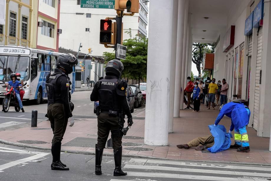 Um paramédico cobre o corpo de um homem que morreu após desmaiar na calçada, durante o surto do coronavírus, em Guayaquil, no Equador