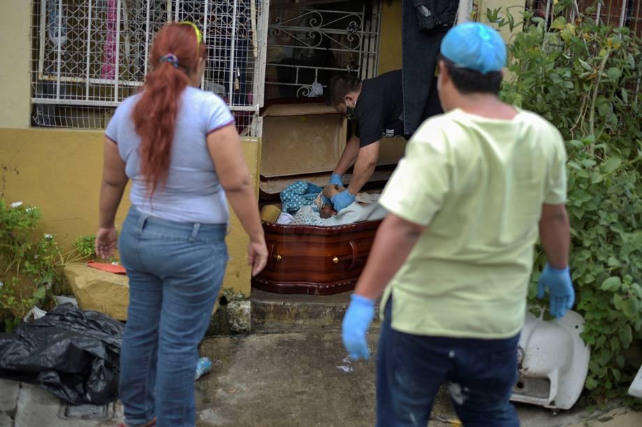 O corpo de uma mulher é colocado dentro de um caixão após morrer em casa durante o surto do coronavírus, em Guayaquil, no Equador
