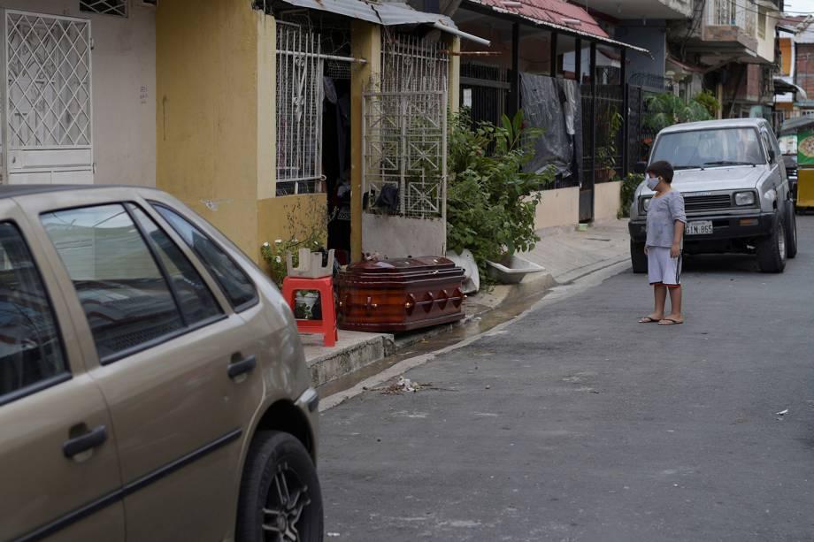 Uma criança observa um caixão com o corpo de uma pessoa que morreu em casa, durante o surto do coronavírus, em Guayaquil, no Equador