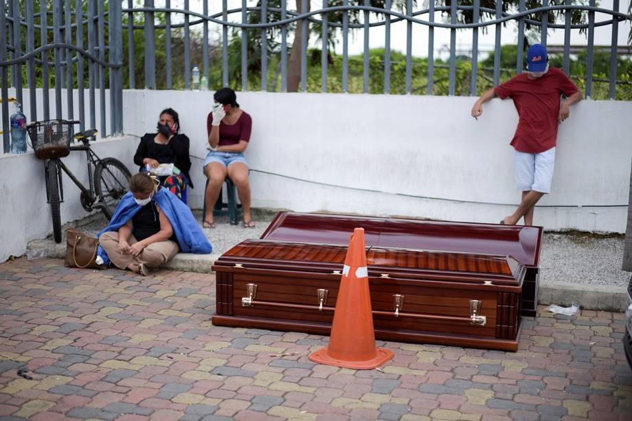 Pessoas esperam ao lado de caixões do lado de fora do Hospital Geral Guasmo Sur, em Guayaquil, no Equador
