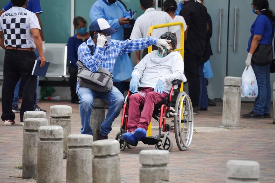 Um homem tem sua máscara de respirar ajustada enquanto espera do lado de fora do Hospital Geral Guasmo Sur, em Guayaquil, no Equador