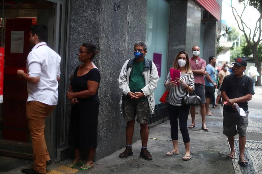 Pessoas esperam na fila para entrar no banco durante o surto do coronavírus, no bairro de Copacabana, no Rio de Janeiro