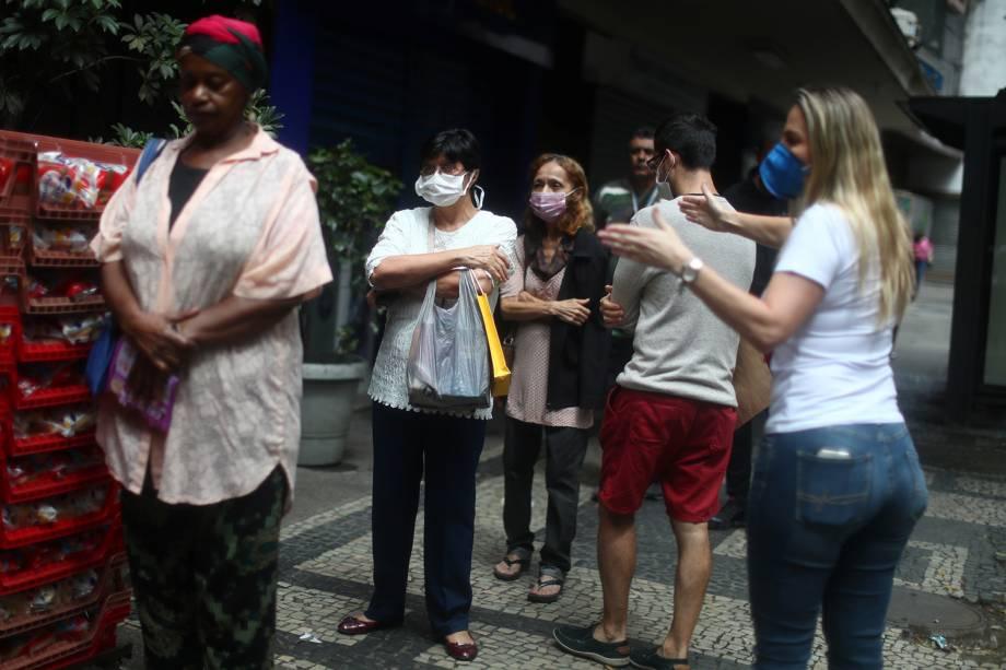 Uma funcionária do banco pede que os clientes mantenham distância enquanto se alinham para entrar no banco durante o surto do coronavírus, no bairro de Copacabana, no Rio de Janeiro