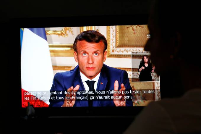French President Emmanuel Macron is seen as he addresses the nation about the coronavirus disease (COVID-19) outbreak, on a television screen