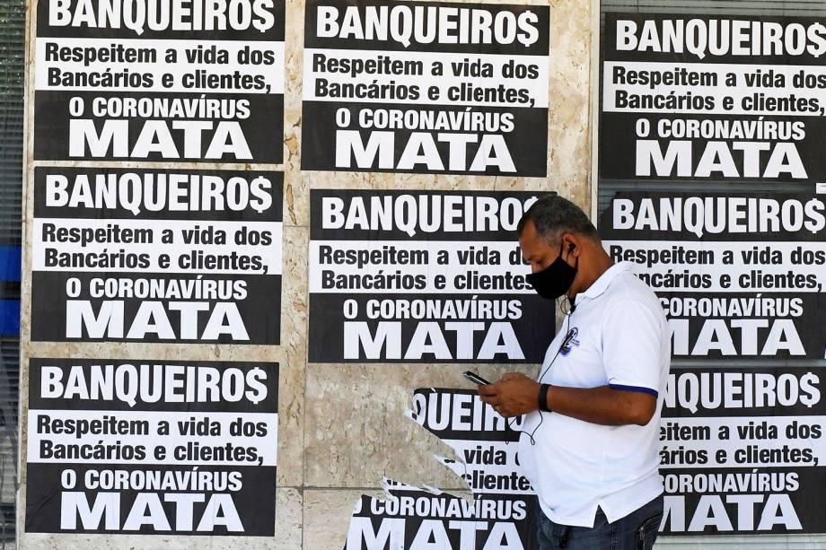 Homem com máscara espera na fila em frente ao banco da Caixa para tentar receber ajuda emergencial do governo federal em meio ao surto do coronavírus, no Rio de Janeiro