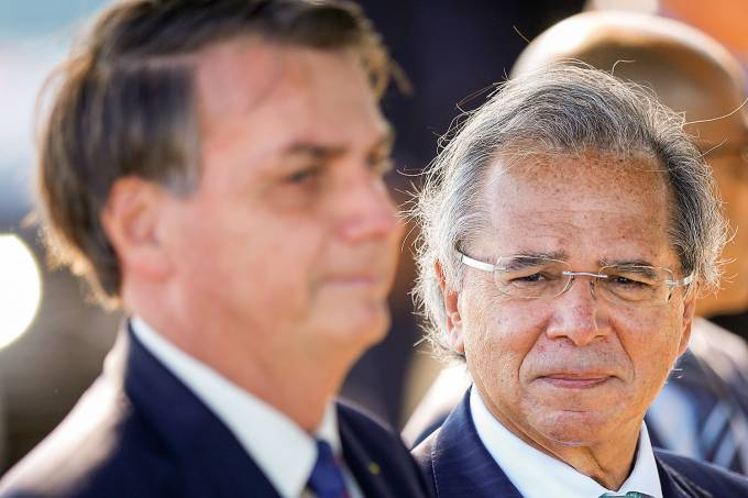 Brazil's Economy Minister Paulo Guedes listens to Brazil's President Jair Bolsonaro, while leaving Alvorada Palace in Brasilia