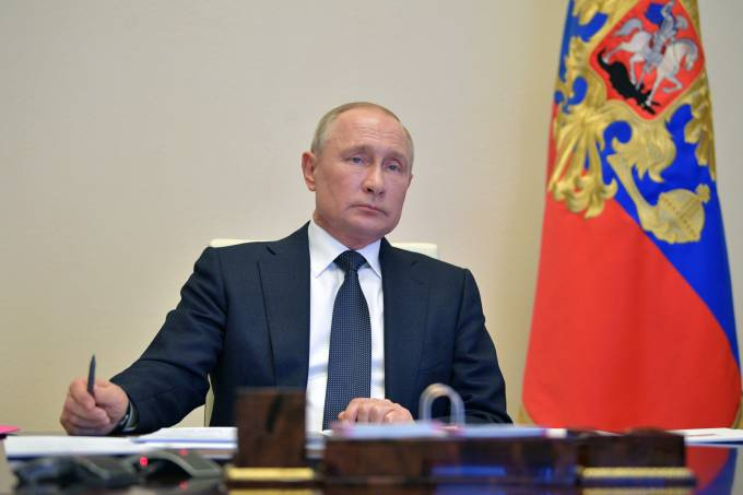 Russian President Vladimir Putin chairs a meeting via a video link outside Moscow