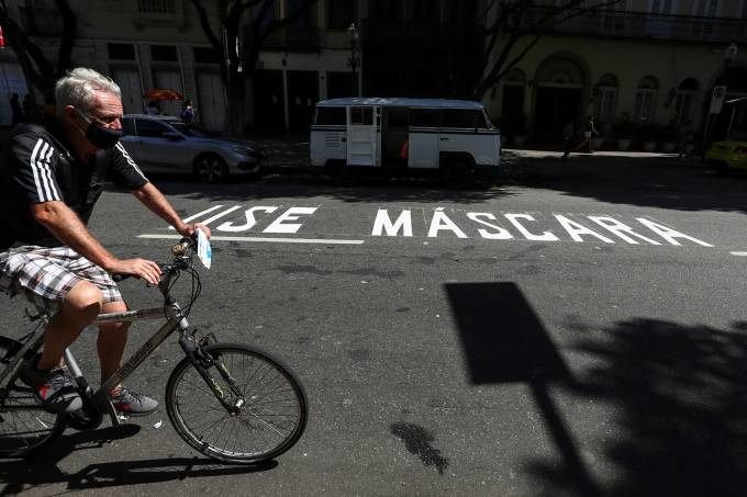 "A man rides a bicycle next to a message reading ""Use mask"" painted on the street, following the coronavirus disease (COVID-19) outbreak, in Rio de Janeiro"